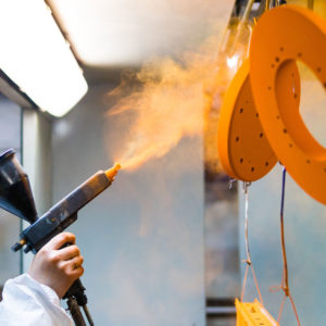 Powder coating of metal parts. A woman in a protective suit sprays powder paint from a gun on metal products